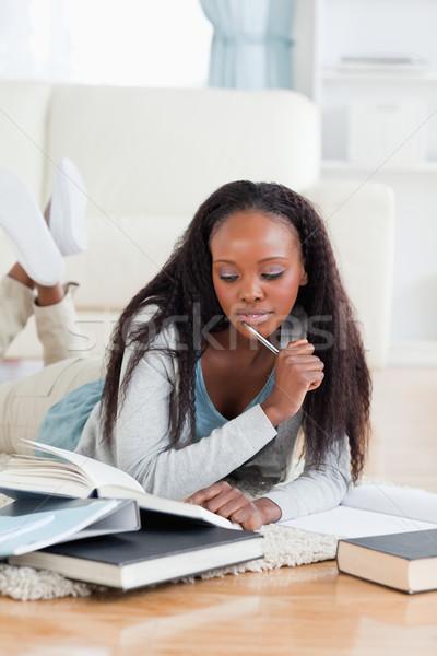 Young female student lying on floor doing homework Stock photo © wavebreak_media