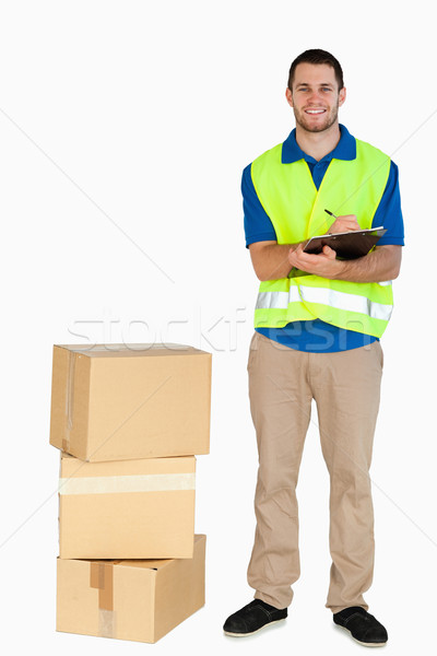 Smiling young delivery man filling in delivery note against a white background Stock photo © wavebreak_media