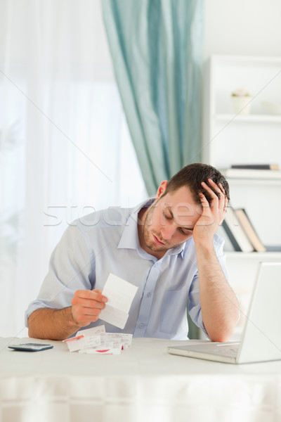 Concerned young businessman looking at an invoice Stock photo © wavebreak_media