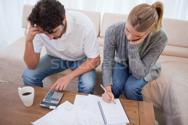 Stock photo: Couple looking at their bills in their living room