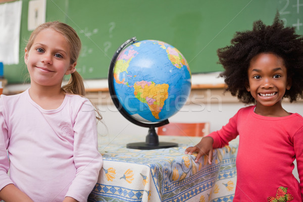 Schoolgirls posing with a globe in a classroom Stock photo © wavebreak_media