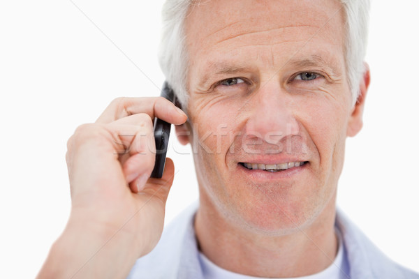 Smiling mature man making a phone call against a white background Stock photo © wavebreak_media