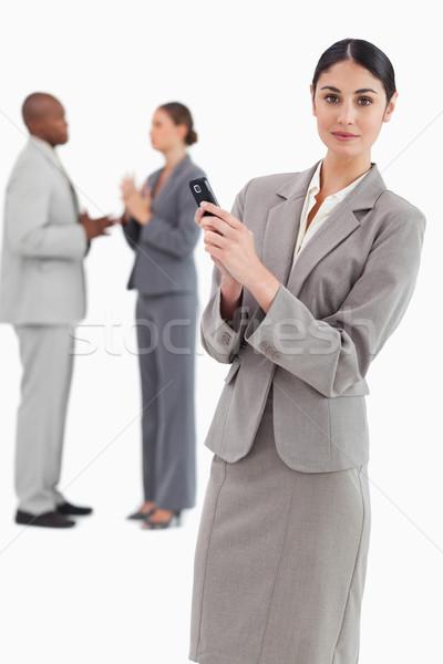Elarusítónő tart mobiltelefon kollégák mögött fehér Stock fotó © wavebreak_media