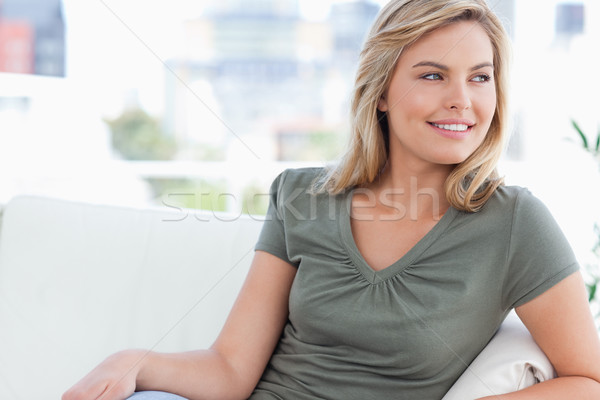 A close up shot of a woman looking sideways while sitting on the couch. Stock photo © wavebreak_media
