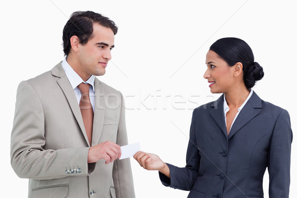 Saleswoman handing business card over to costumer against a white background Stock photo © wavebreak_media