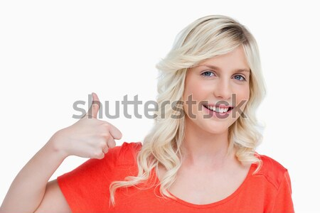 Stock photo: Smiling young blonde woman putting her thumbs up against a white background
