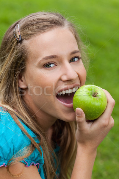 Young happy woman looking at the camera while eating a delicious green apple Stock photo © wavebreak_media