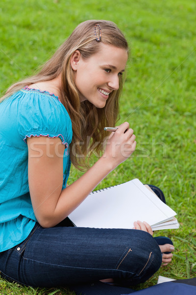 Smiling student looking towards the side while seriously writing on her notebook Stock photo © wavebreak_media