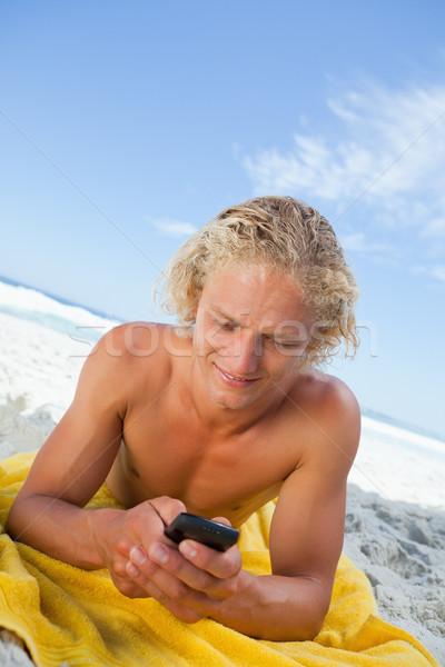 Szőke nő férfi strand törölköző küldés szöveg tengerpart Stock fotó © wavebreak_media