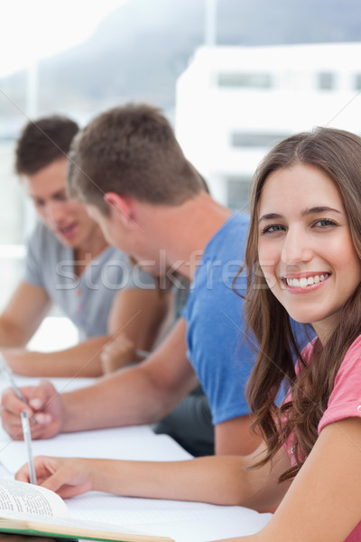 A close up shot of a smiling woman as her friends work in the background  Stock photo © wavebreak_media