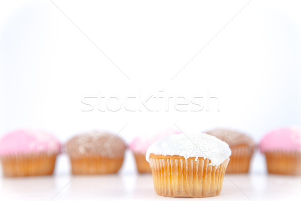 White muffin placed in front of a line of muffin with icing sugar against a blue background Stock photo © wavebreak_media