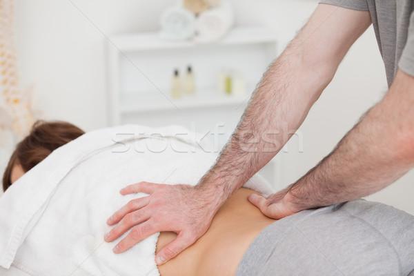Masseur massaging the back of a woman in a room Stock photo © wavebreak_media
