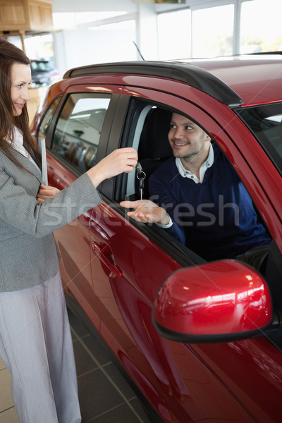 Stock photo: Businesswoman giving car keys to a customer in a garage