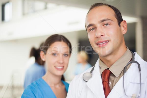 Doctor and nurse looking at camera in hospital corridor Stock photo © wavebreak_media