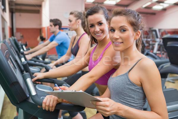 Сток-фото: спортзал · инструктор · женщину · улыбаясь · осуществлять · велосипед