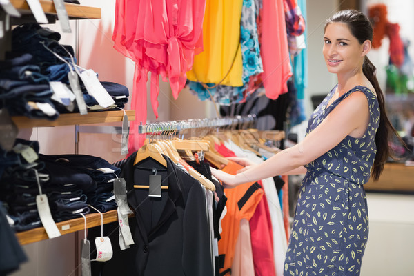 Woman standing at a clothes rail in the clothes store Stock photo © wavebreak_media