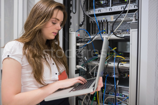 Woman using laptop to work on servers in data center Stock photo © wavebreak_media