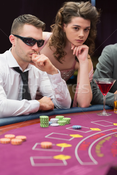 Stock photo: Man and woman at poker table in casino