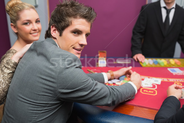 Couple smiling as man is taking his winnings in casino  Stock photo © wavebreak_media