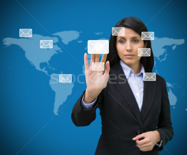 Businesswoman selecting holographic email symbol from many against blue world map Stock photo © wavebreak_media