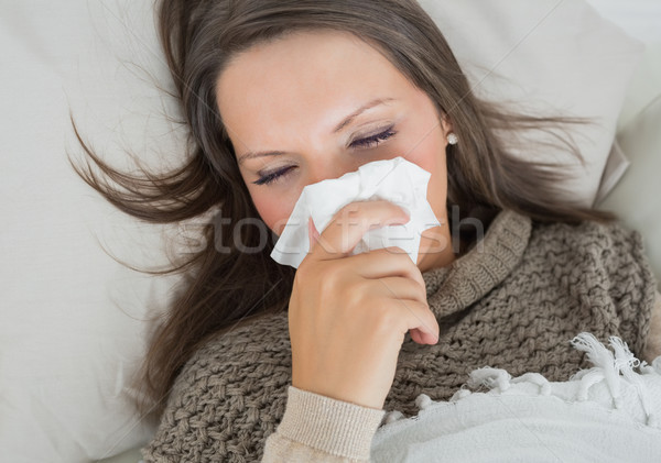 Sick woman lying on sofa and blowing nose in the living room Stock photo © wavebreak_media