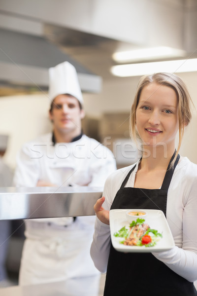 Smiling waitress presenting salmon dish with chef standing behind her Stock photo © wavebreak_media