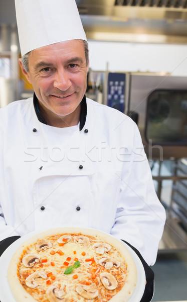 Smiling chef showing mushroom pizza Stock photo © wavebreak_media