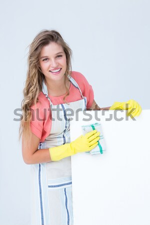 Smiling woman in apron and rubber gloves cleaning white surface Stock photo © wavebreak_media