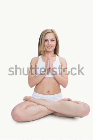 Portrait of young woman with crossed legs in praying position Stock photo © wavebreak_media