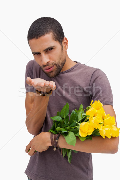 Handsome man blowing a kiss and holding roses Stock photo © wavebreak_media