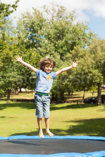 Happy boy jumping high on trampoline in the park Stock photo © wavebreak_media