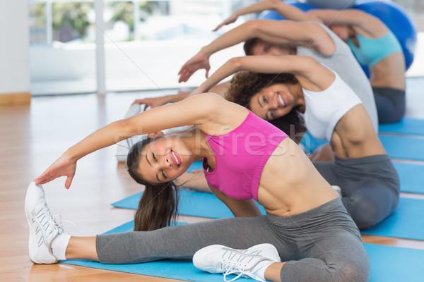 Sporty people doing stretching exercises in fitness studio Stock photo © wavebreak_media