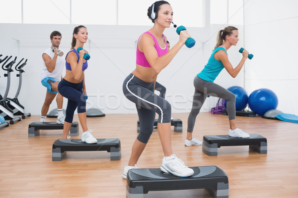 Class performing step aerobics exercise with dumbbells Stock photo © wavebreak_media