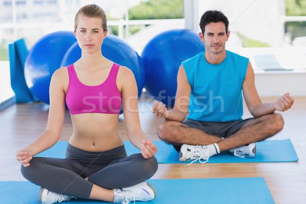 Young couple sitting in lotus posture at fitness studio Stock photo © wavebreak_media