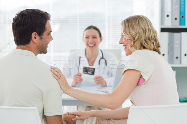 Expectant couple with doctor in clinic Stock photo © wavebreak_media