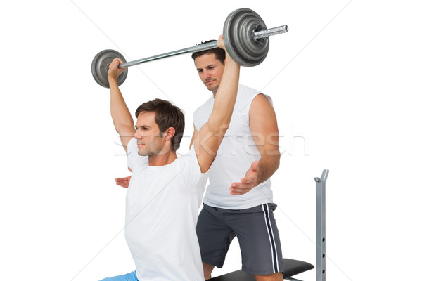 Trainer helping fit man to lift the barbell bench press Stock photo © wavebreak_media