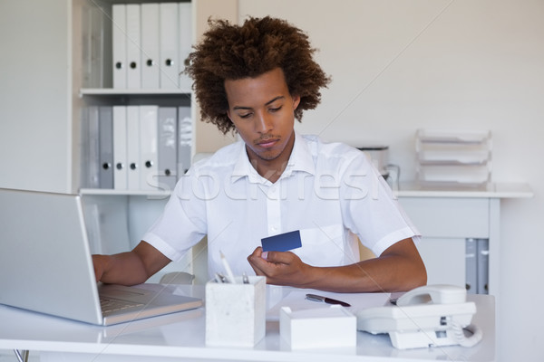 Relaxed casual businessman shopping online at his desk Stock photo © wavebreak_media