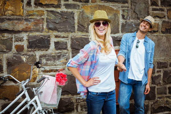 Hip young couple standing by brick wall with their bikes Stock photo © wavebreak_media