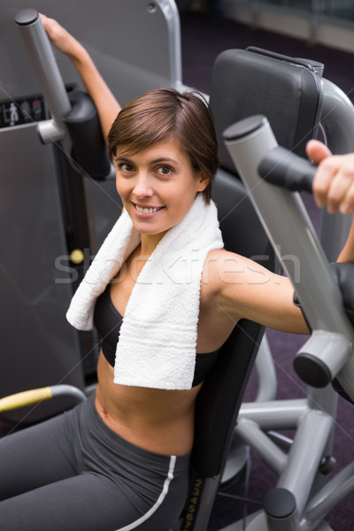 Happy brunette using weights machine for arms Stock photo © wavebreak_media
