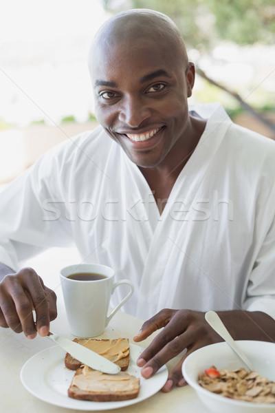 Knappe man badjas ontbijt buiten huis Stockfoto © wavebreak_media