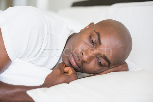 Unhappy man lying in bed Stock photo © wavebreak_media