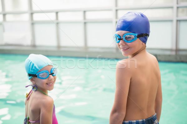 Cute little siblings standing poolside Stock photo © wavebreak_media