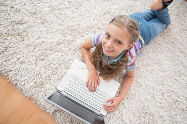 Cute girl using laptop while lying on rug Stock photo © wavebreak_media