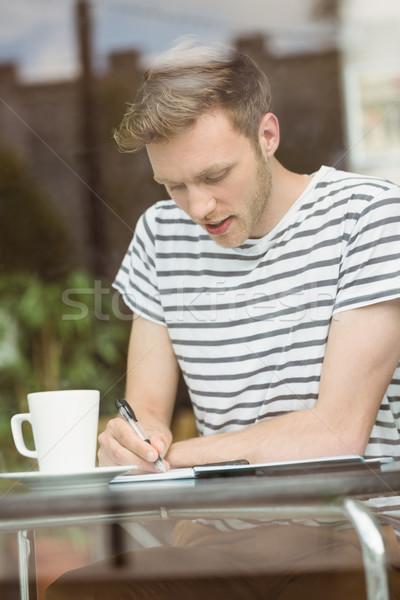 Sorridente estudante sessão bebida quente escrita bloco de notas Foto stock © wavebreak_media