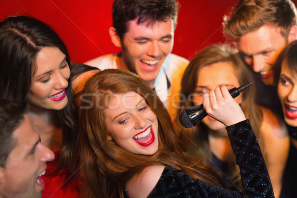 Happy friends singing karaoke together Stock photo © wavebreak_media