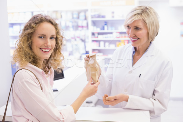 Pharmacist giving bag paper to costumer  Stock photo © wavebreak_media