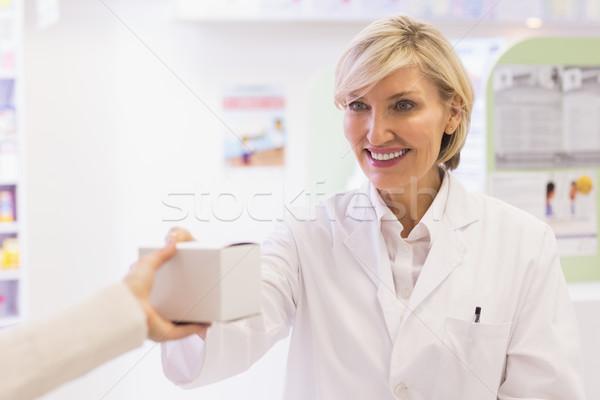 Stock photo: Pharmacist taking medicine to costumer