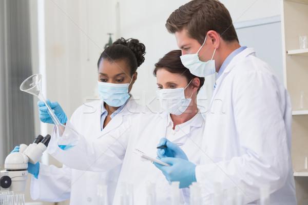 Regarder bécher prendre des notes laboratoire médicaux Photo stock © wavebreak_media