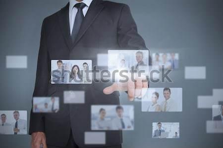 Composite image of businessman pointing his finger at camera Stock photo © wavebreak_media