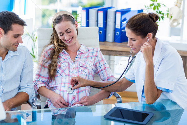 Stock photo: Doctor checking belly of pregnant woman with stethoscope
